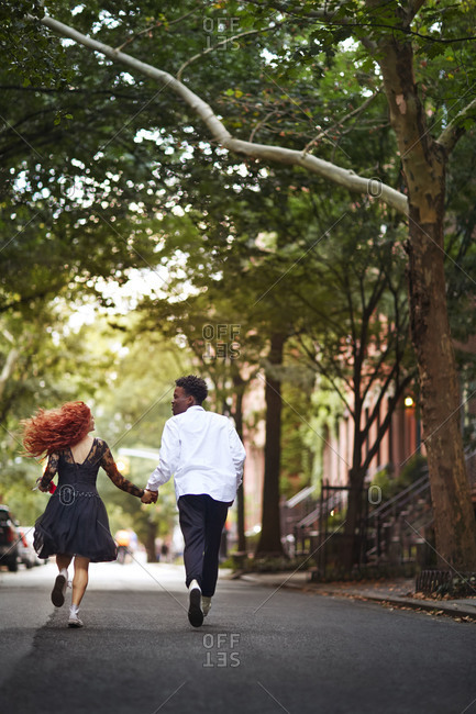 A couple in dress clothes running down street