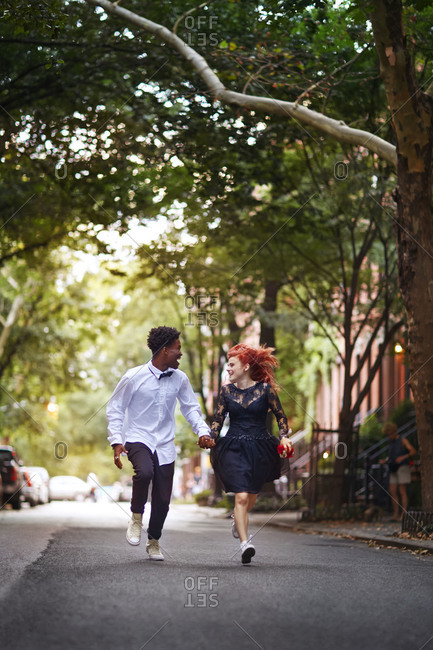 A couple in dress clothes running up  street
