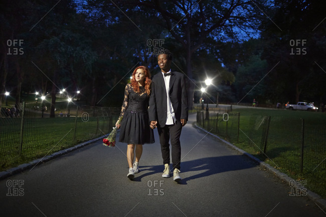 Couple strolling in park at night