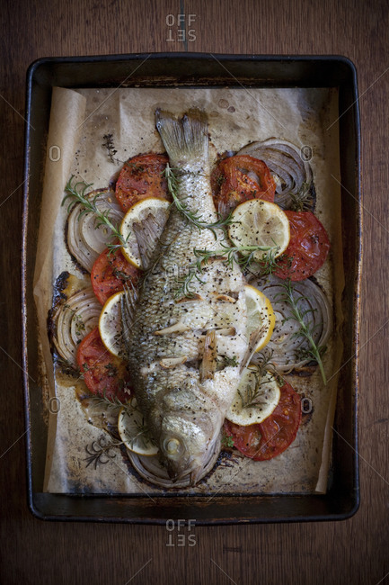 A baked fish sits in a pan