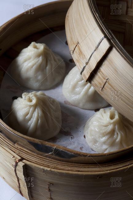 A steaming basket opens slightly to reveal dumplings