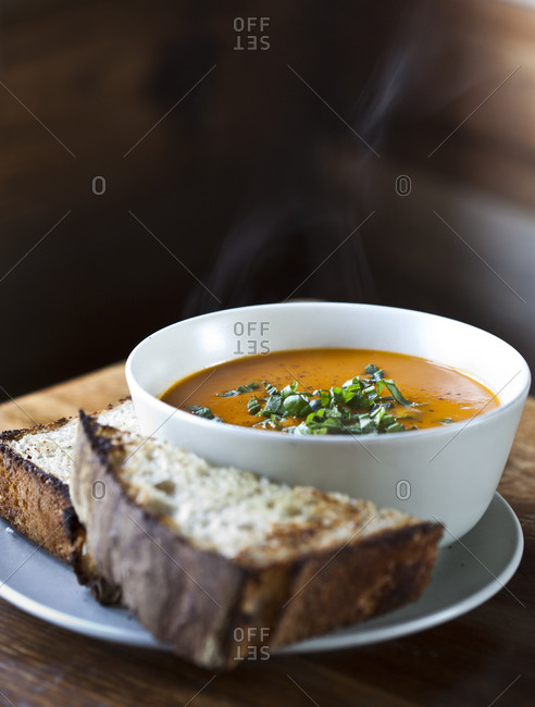 A bowl of soup sits next to two pieces of bread
