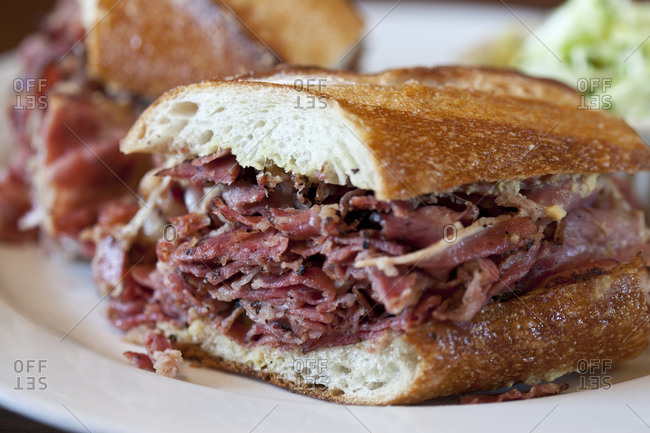 A hot pastrami sandwich sits on a plate
