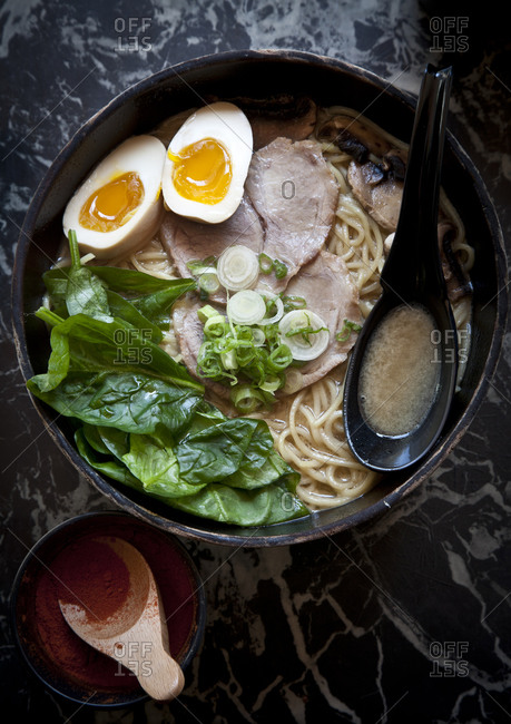 An egg and pork belly float in a bowl of ramen soup