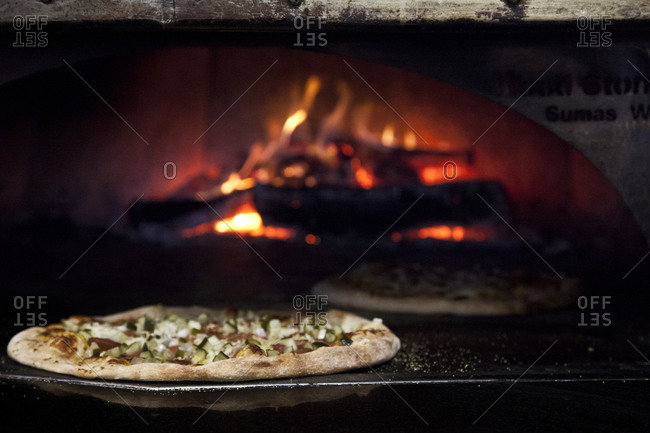 Sausage Pizza with mozzarella cooks in a wood-fire oven