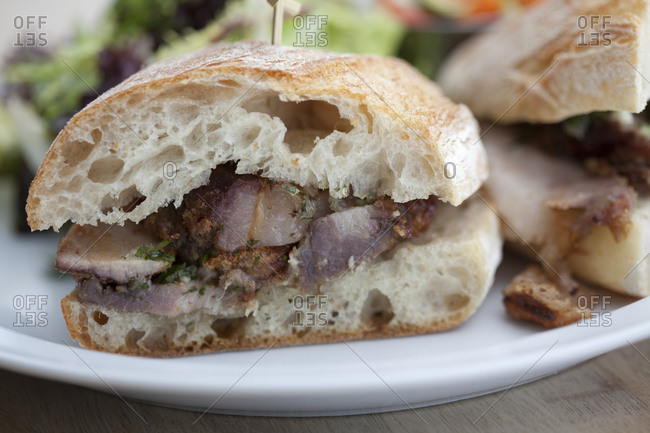A Porchetta sandwich sits on a plate