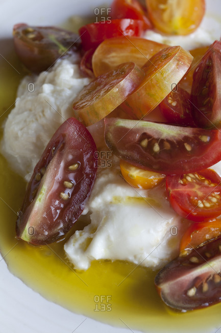 Burrata and cherry tomatoes sit in olive oil