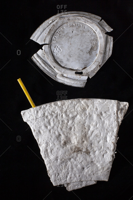 A styrofoam cup lays on a black background