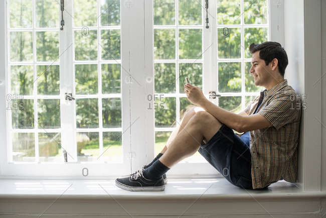 Man sitting by a window, holding a cell phone
