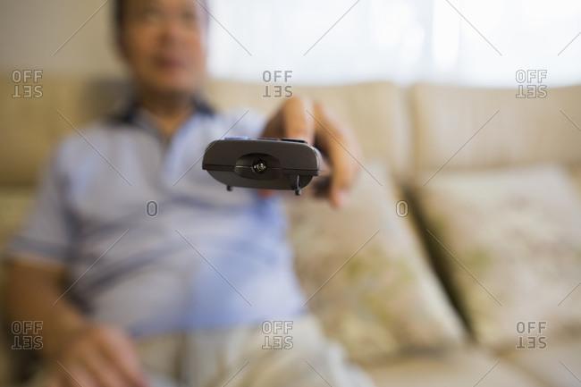 Man sitting on sofa holding remote control