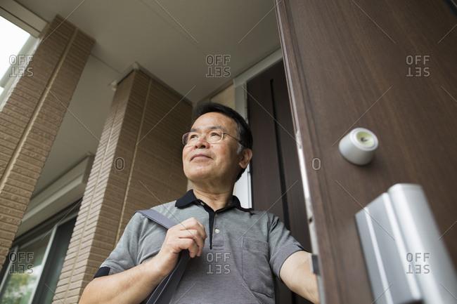 A man standing at his front door