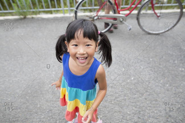 A young girl with pigtails smiling at the camera
