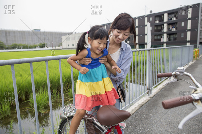 A mother lifting her daughter onto a bicycle