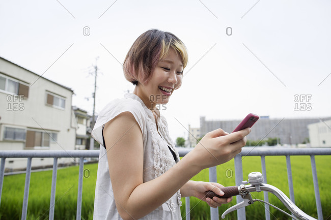 A woman pushing a bicycle while looking at her cell phone