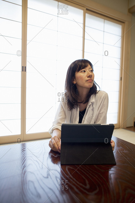 A woman sitting at a table with a laptop computer