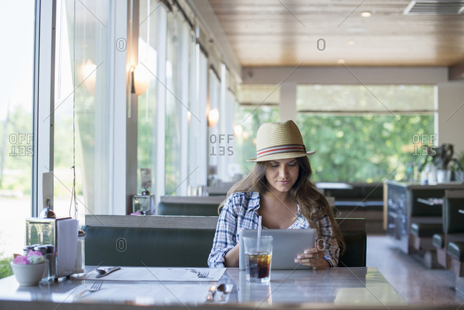 A young woman seated at a table in a diner, wearing a straw hat using a digital tablet