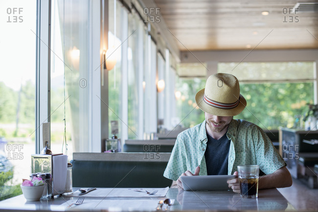 A man wearing a hat sitting in a diner using a digital tablet