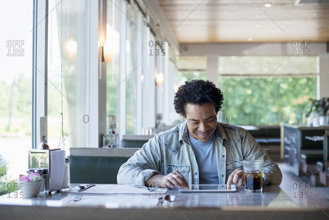A man sitting in a diner using a digital tablet