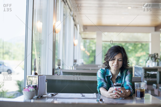 A woman in a checked shirt sitting at a table, laughing and looking at her smart phone