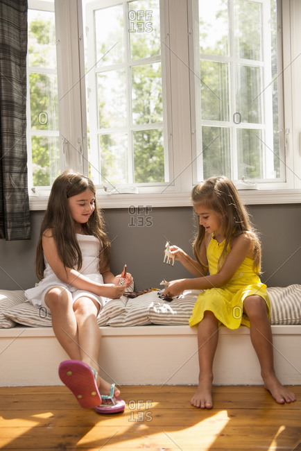 Two girls playing together, sitting on a window seat indoors