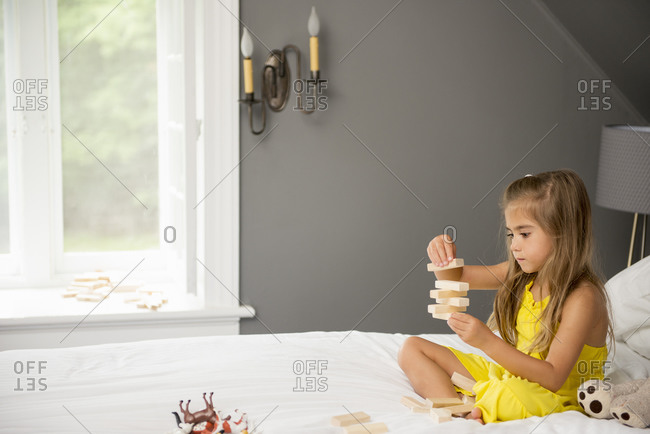 A girl sitting on a bed, playing with building blocks