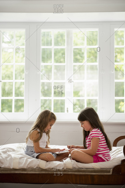 Two girls sitting and playing, using a digital tablet