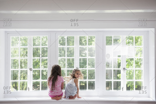 Two girls sitting side by side by a large window