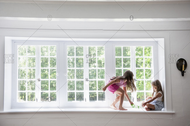 Two girls playing, sitting on a ledge by a large window