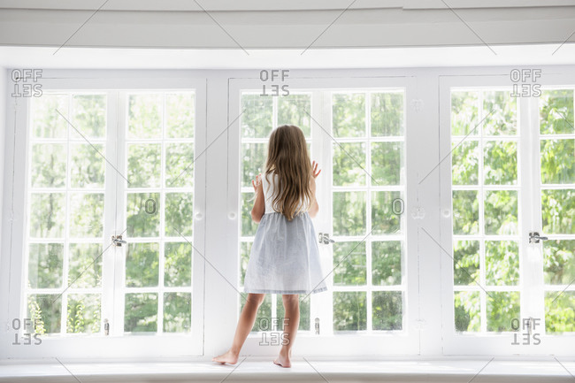A child standing at a window looking out