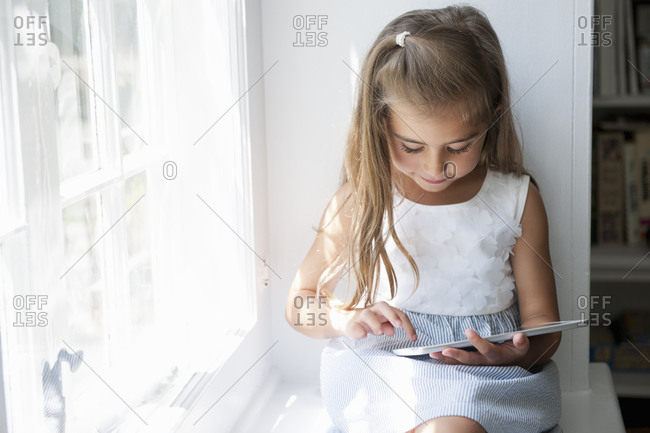 A young girl sitting at a window seat, using a digital tablet