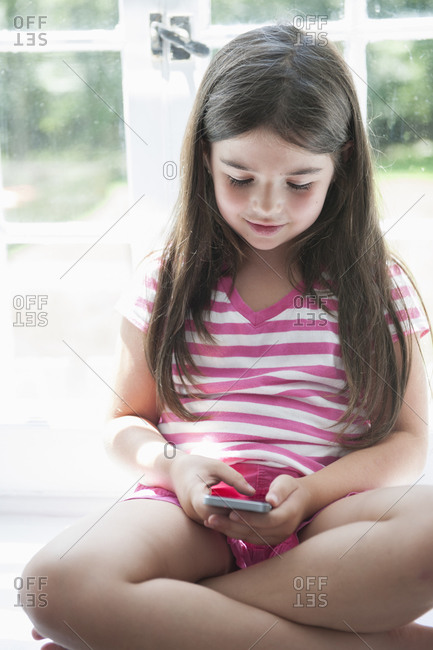 A girl sitting playing, holding a smart phone