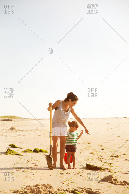 Mother and daughter collecting clams on the beach