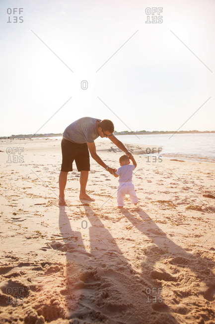 Little boy walking on the beach with his father