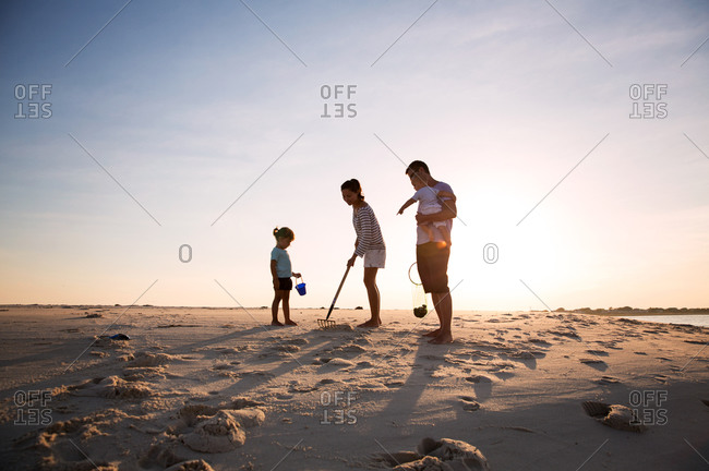 Family searching for clams on the beach
