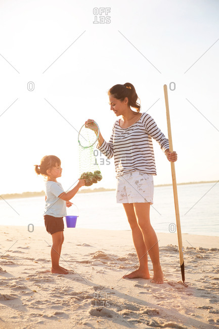 Mother and daughter collecting shells on the beach
