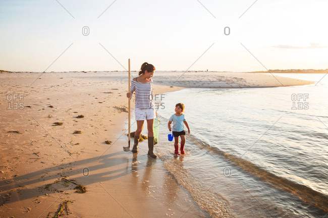 Woman and daughter collecting shells on the beach
