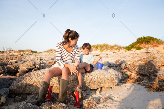 Mother dusting sand off the feet of her daughter on the beach