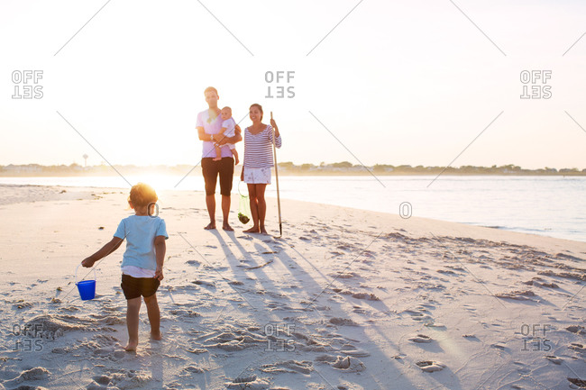Family spending time at a beach at sunset