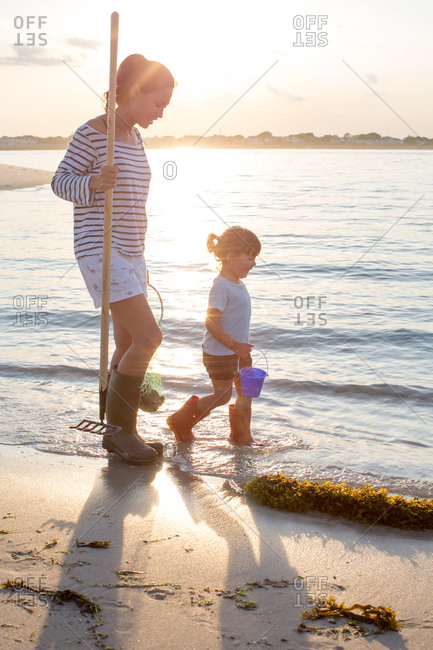 Girl and her mother collecting shells at sunset