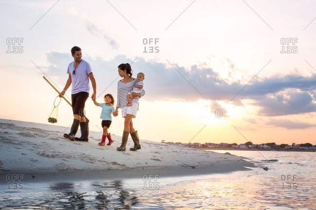 Family walking hand in hand on the beach