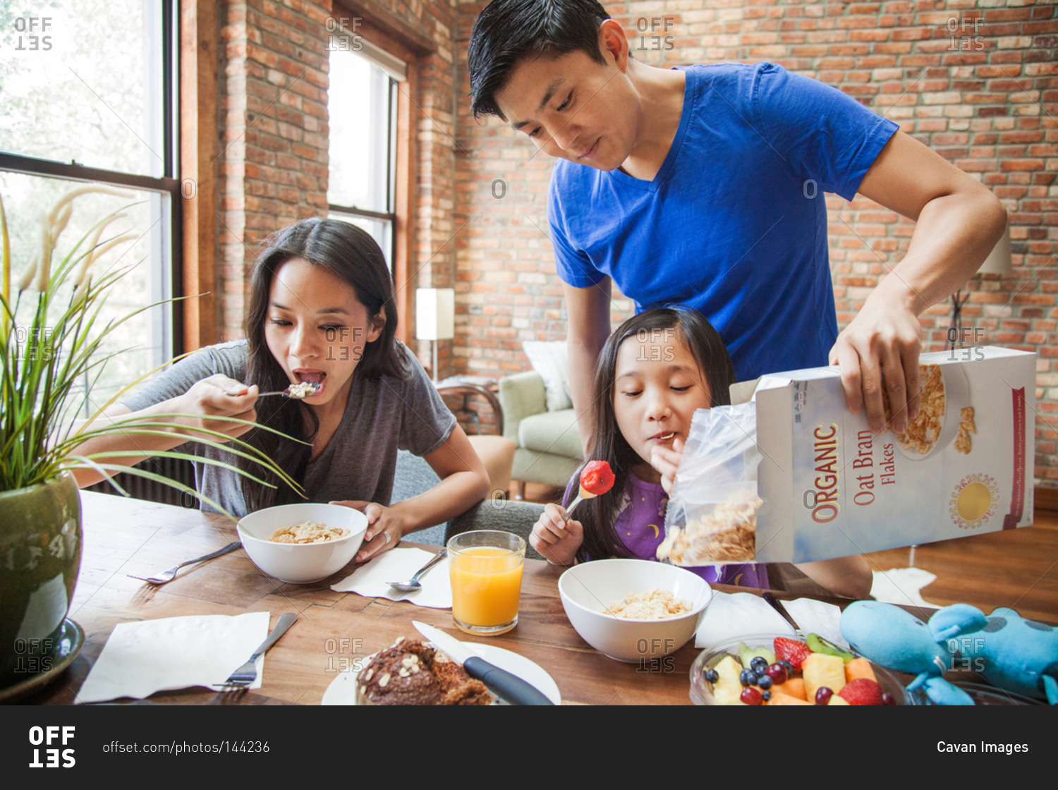 Family eating cereal for breakfast stock photo - OFFSET