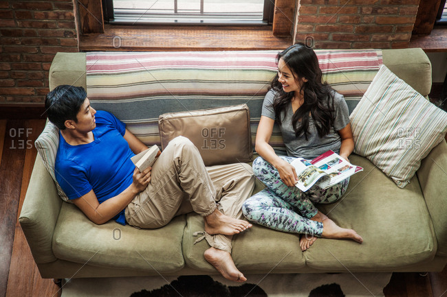 High angle view of couple reading on couch