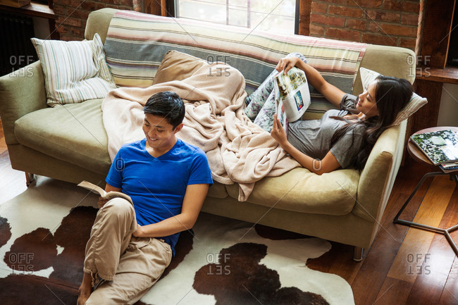 High angle view of couple reading in living room