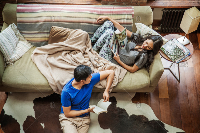 High angle view of couple resting in living room