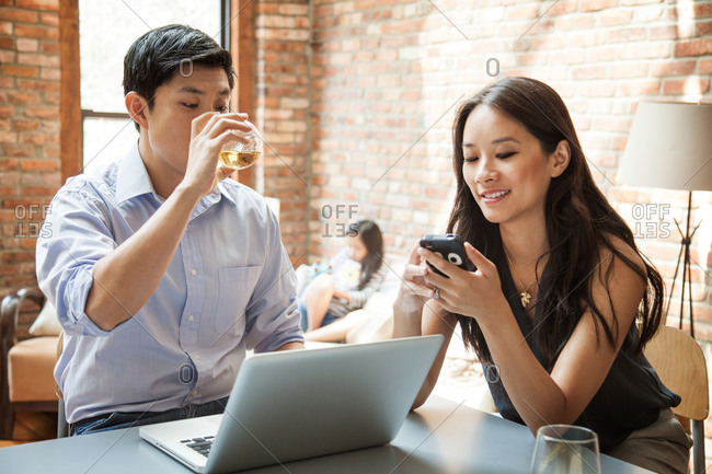 Couple sitting by a table and using their digital devices