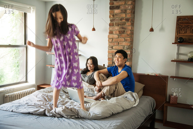 Young girl bouncing on her parents bed