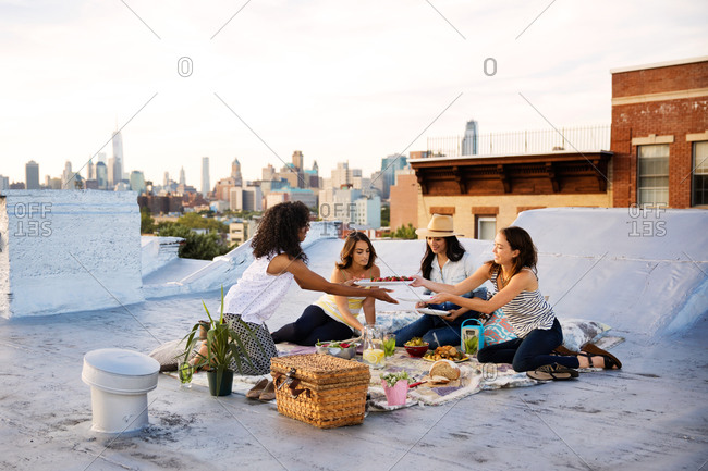 Young women having dinner on a rooftop in Brooklyn
