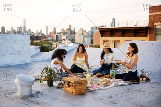 Young women having a picnic on a rooftop in Brooklyn