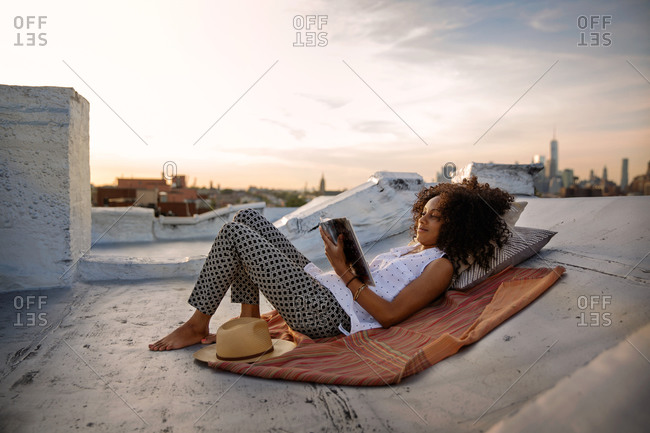 Young woman reading a book on a rooftop