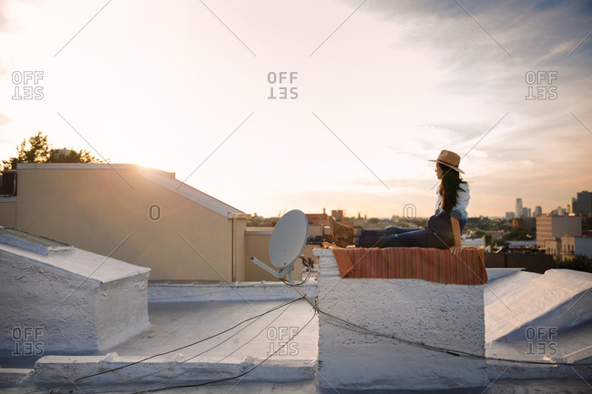 Woman watching the sunset from a rooftop in Brooklyn